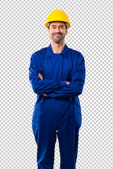 Jeune ouvrier avec casque en gardant les bras croisés en position frontale. expression confiante
