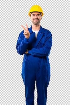 Jeune ouvrier avec casque heureux et comptant avec deux doigts