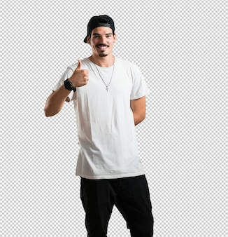Jeune rappeur homme gai et excité, souriant et levant le pouce, succès et approbation, geste ok