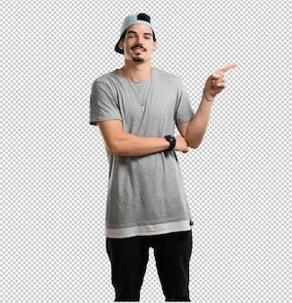 Jeune rappeur homme pointant vers le côté, souriant surpris présentant quelque chose, naturel et décontracté