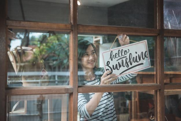 Jolie femme d'affaires asiatique en tournant le signe ouvert de sa boutique