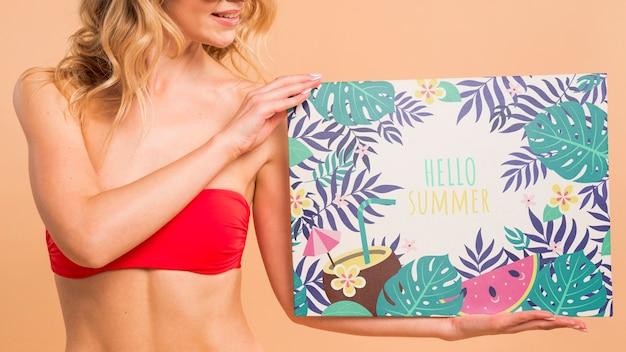 Jolie femme en bikini présentant la maquette de la couverture