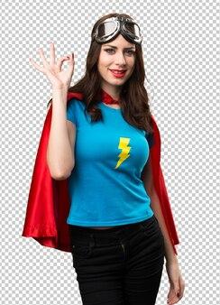 Jolie fille de super-héros faisant signe ok