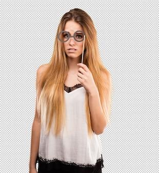 Jolie jeune femme à l'aide de lunettes de fête