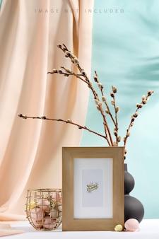 Joyeuses pâques oeufs et branches sceaux dans un vase avec tissu de draperie et cadre de maquette