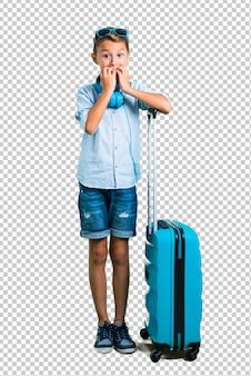 Kid avec des lunettes de soleil et un casque voyageant avec sa valise est un peu nerveux et effrayé
