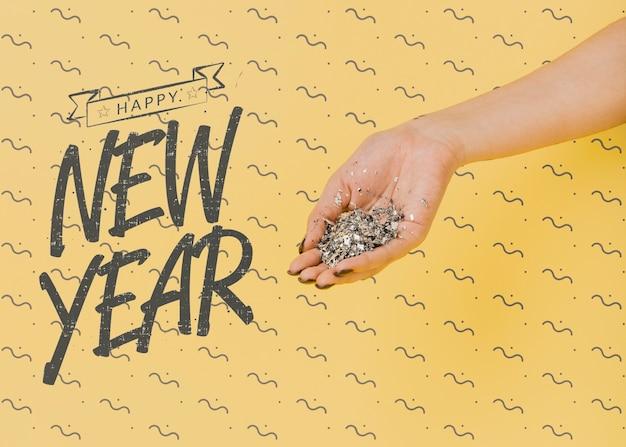 Lettrage de nouvel an avec une personne tenant des confettis d'argent