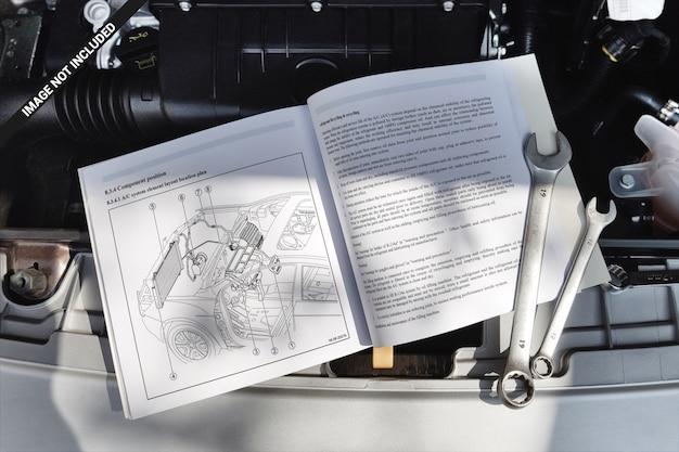 Livre à couverture souple ouvert allongé sur une maquette de moteur de voiture