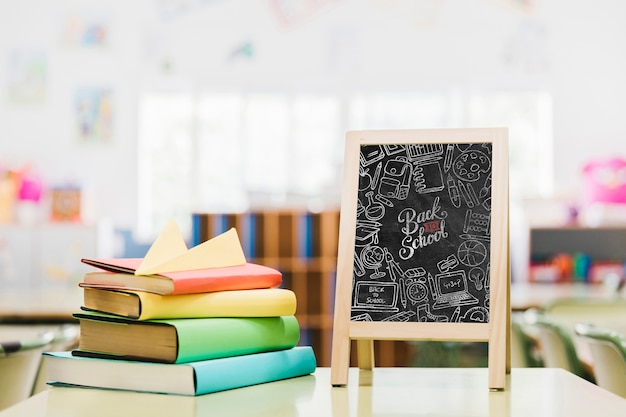 Livres colorés à côté de la maquette du tableau d'école