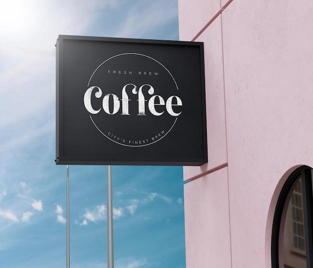 Logo maquette boîte noire signe façade sur bâtiment rose