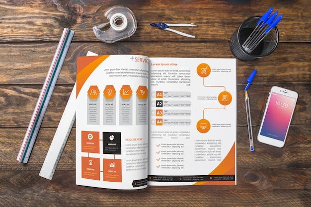 Magazine et maquette de smartphone sur une table en bois avec des stylos et des règles