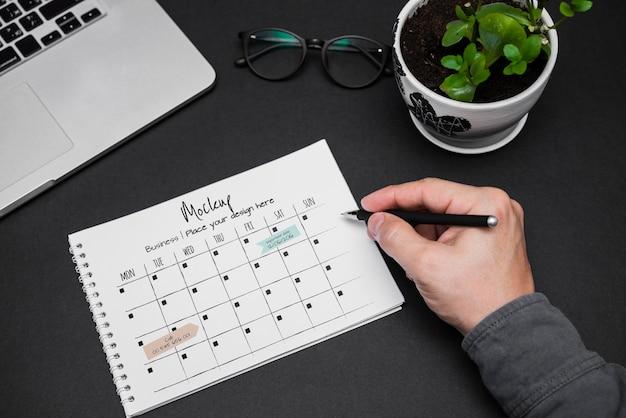 La main de l'homme écrit sur le calendrier