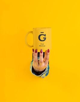 Main avec maquette de tasse