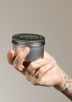 Main tatouée tenant une maquette psd de pot de crème pour le visage