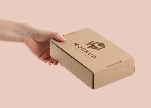 Main tenant une maquette de boîte