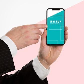 Main tenant une maquette de smartphone