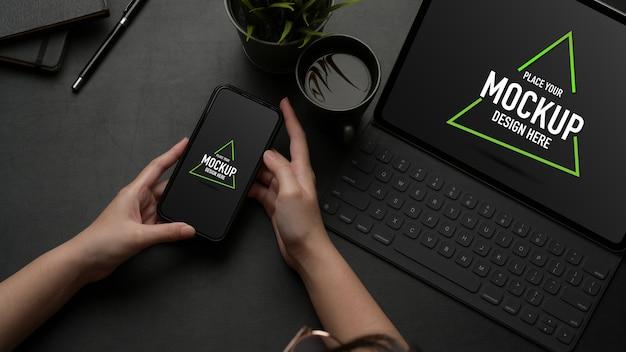 Mains à l'aide d'une maquette de smartphone sur une table de travail avec une maquette de tablette et une tasse de café