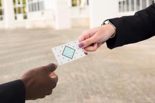 Mains échangeant une carte de visite
