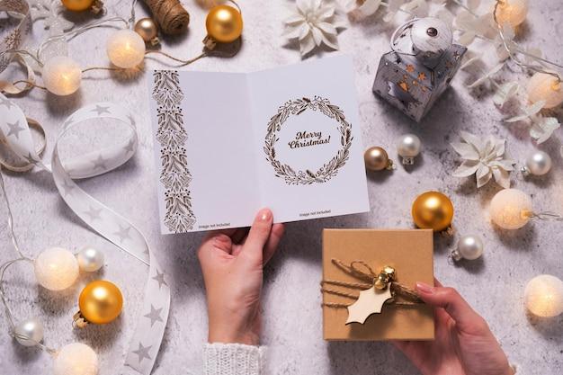 Des mains féminines tiennent une carte de noël et une boîte-cadeau. entouré de décorations et de lumières de noël. maquette