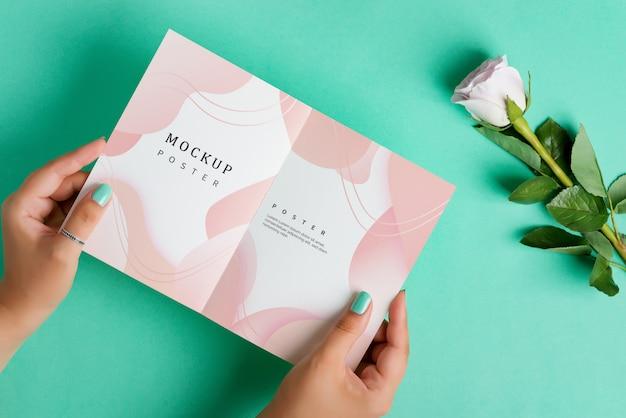 Les mains de la femme tiennent une brochure maquette vide avec rose