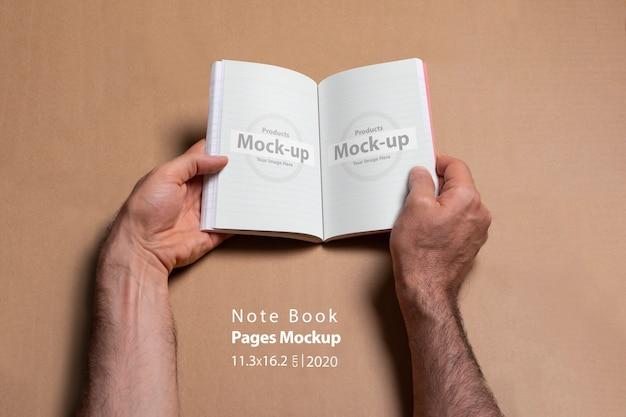 Mains mâles tenant un carnet de notes ouvert avec des pages blanches
