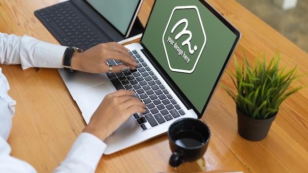 Mains tapant sur le clavier d'ordinateur portable maquette près de la tasse de café