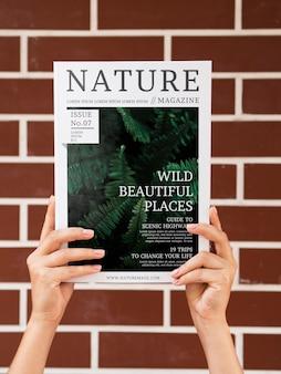 Mains tenant un magazine de la nature maquette