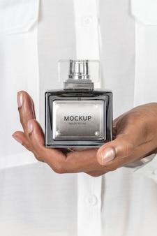 Mains tenant une maquette de bouteille en verre de parfum vierge