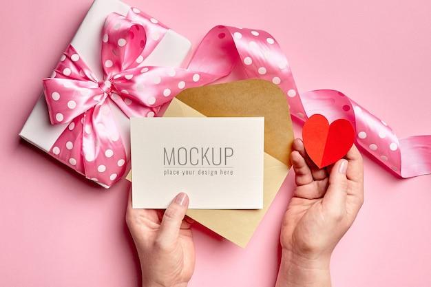 Mains tenant la maquette de la carte de la saint-valentin avec boîte-cadeau et coeur en papier
