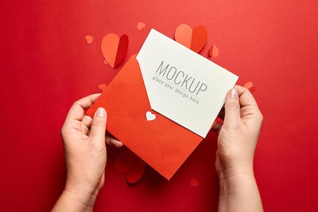 Mains tenant la maquette de la carte saint valentin avec des coeurs en papier sur rouge