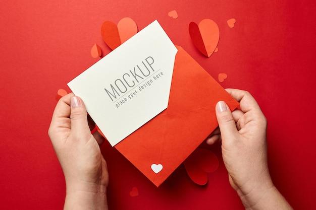 Mains tenant la maquette de la carte de la saint-valentin avec des coeurs en papier