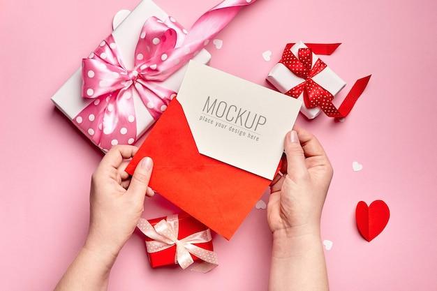 Mains tenant la maquette de la carte de la saint-valentin avec des coffrets cadeaux