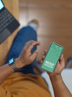 Mâle main à l'aide de smartphone maquette alors qu'il était assis dans la salle de bureau