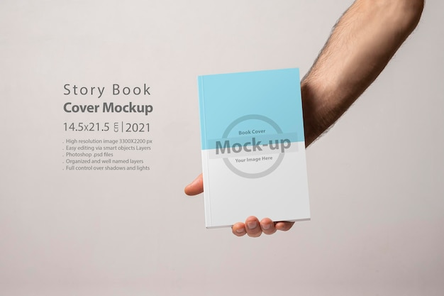 Mâle main tenant un livre-catalogue fermé avec maquette de couverture vierge