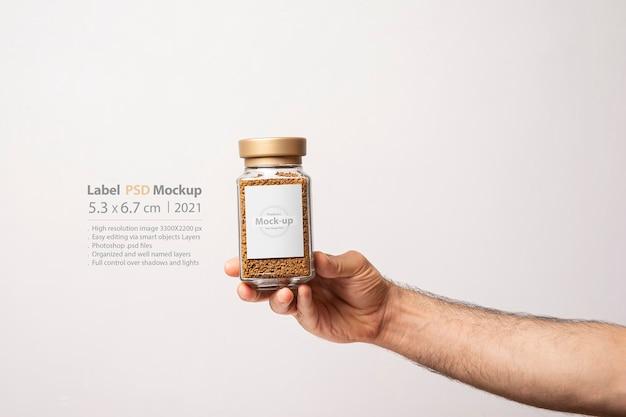 Mâle main tenant un pot en verre de café instantané avec étiquette vierge