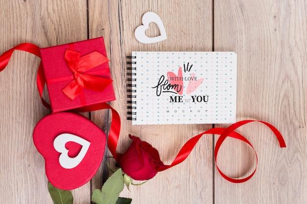 Maquette bloc-notes à côté de coffrets cadeaux pour la saint-valentin