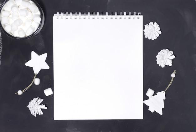 Maquette de bloc-notes avec des décorations blanches sur un tableau noir