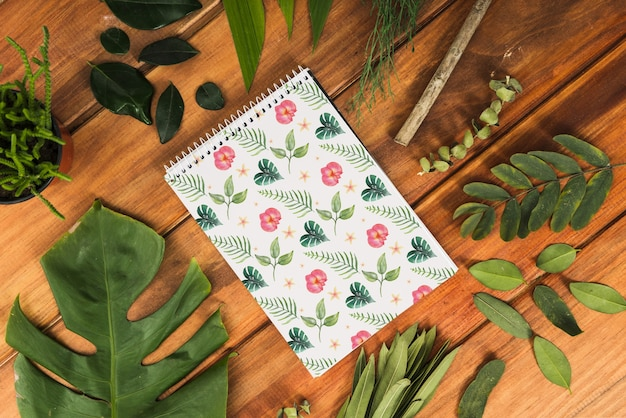 Maquette bloc-notes avec des feuilles tropicales