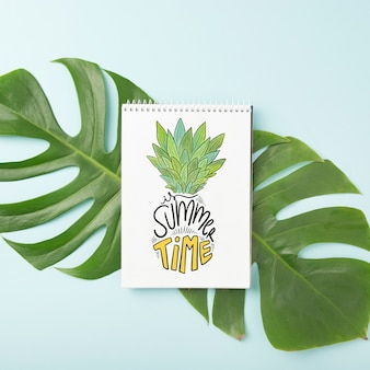 Maquette de bloc-notes en spirale sur feuille de palmier
