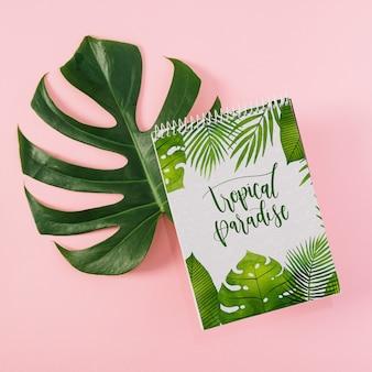 Maquette de bloc-notes en spirale sur feuilles de palmier