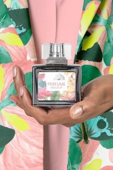 Maquette de bouteille de parfum psd dans la main des femmes