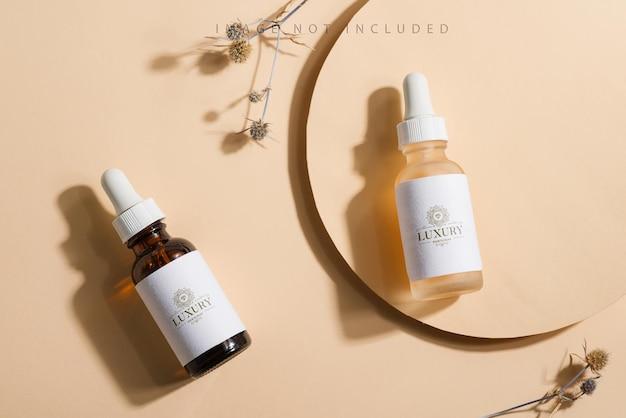Maquette de bouteilles cosmétiques avec un compte-gouttes sur une surface beige avec un soleil éclatant et des ombres dures.
