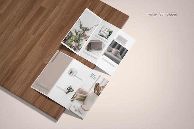 Maquette de brochure à trois volets près d'une planche de bois