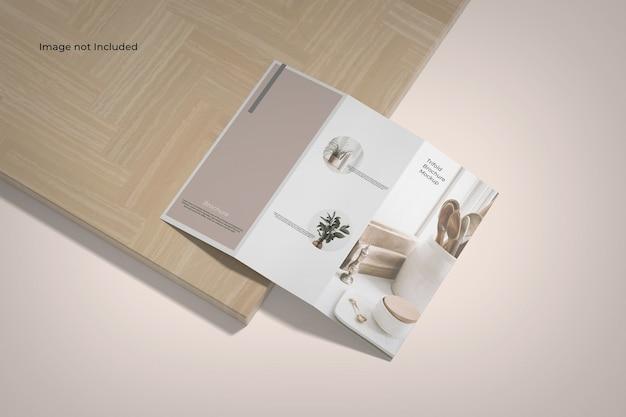 Maquette de brochure à trois volets vue grand angle près d'une planche de bois