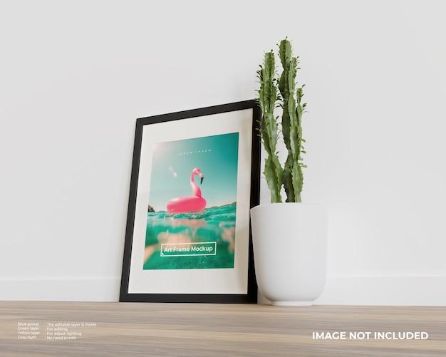 Maquette de cadre d'art sur le plancher en bois avec une plante de cactus