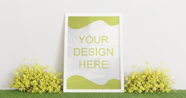 Maquette de cadre blanc debout sur un tapis d'herbe avec quelques plantes décoratives. cadre horizontal