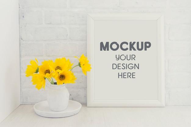 Maquette de cadre blanc vide avec un bouquet de fleurs de tournesol jaune dans un vase vintage