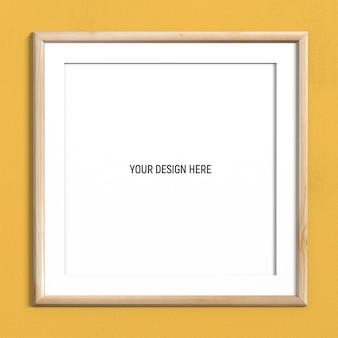 Maquette de cadre en bois carré clair sur un mur texturé jaune
