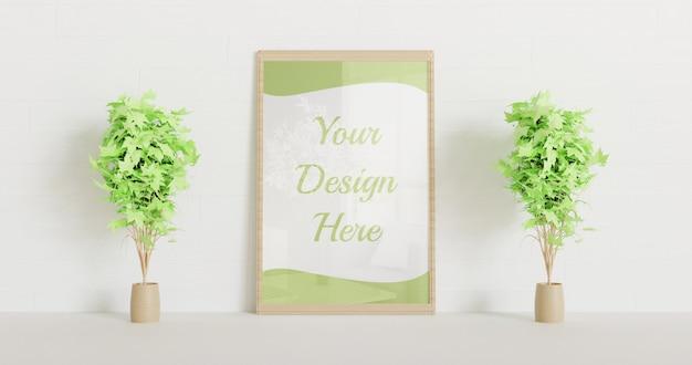 Maquette de cadre en bois debout sur le mur blanc avec quelques plantes décoratives
