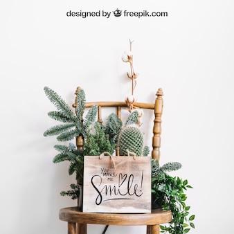 Maquette de cadre sur une chaise avec des fleurs et des cactus